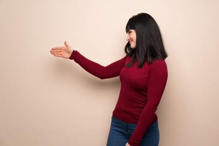 Photo for Young woman with red turtleneck handshaking after good deal - Royalty Free Image
