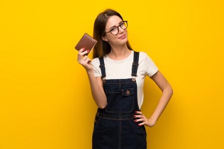 Photo pour Woman over yellow wall holding a wallet - image libre de droit