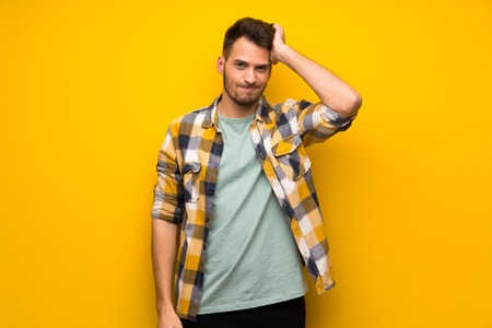 Photo pour Handsome man over yellow wall with an expression of frustration and not understanding - image libre de droit