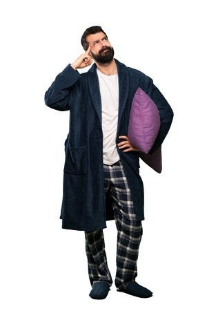 Foto de Man with beard in pajamas having doubts and thinking over isolated white background - Imagen libre de derechos