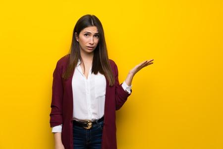 Foto de Young woman over yellow wall making doubts gesture - Imagen libre de derechos