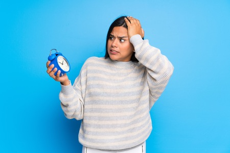 Photo pour Young Colombian girl with sweater restless because it has become late and holding vintage alarm clock - image libre de droit