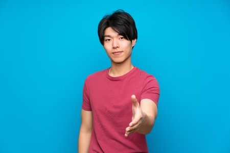 Photo for Asian man with red shirt over isolated blue wall handshaking after good deal - Royalty Free Image