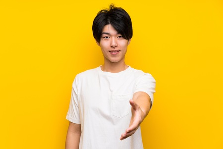 Photo for Asian man over isolated yellow wall shaking hands for closing a good deal - Royalty Free Image