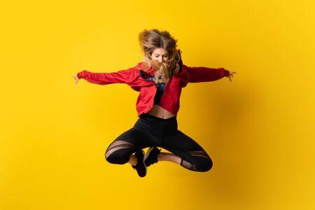 Foto de Urban Ballerina dancing over isolated yellow background and jumping - Imagen libre de derechos