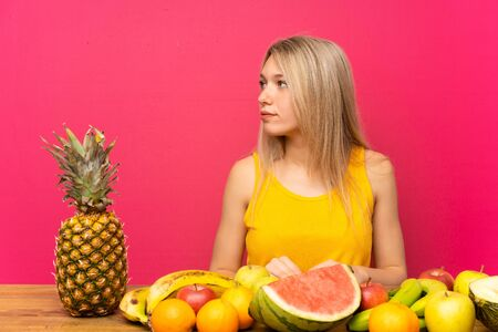 Photo for Young blonde woman with lots of fruits looking side - Royalty Free Image