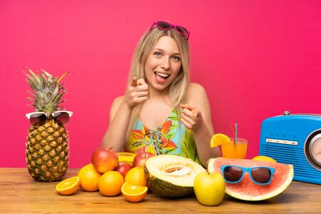 Photo for Young blonde woman with lots of fruits points finger at you - Royalty Free Image