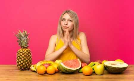 Photo for Young blonde woman with lots of fruits pleading - Royalty Free Image