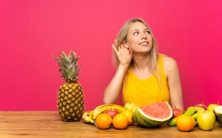 Photo for Young blonde woman with lots of fruits listening something - Royalty Free Image