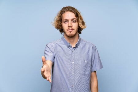 Photo for Blonde man over isolated blue wall handshaking after good deal - Royalty Free Image