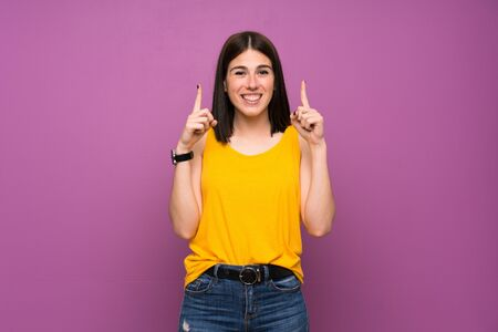Photo pour Young woman over isolated purple wall pointing up a great idea - image libre de droit