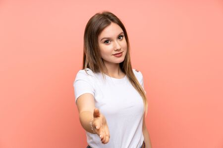 Photo for Teenager girl over isolated pink wall handshaking after good deal - Royalty Free Image
