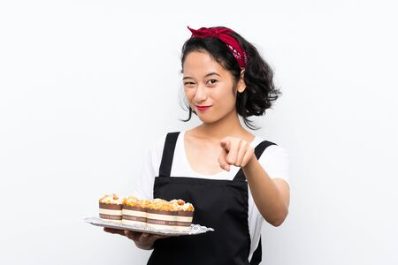 Photo for Young asian girl holding lots of muffin cake over isolated white background points finger at you with a confident expression - Royalty Free Image