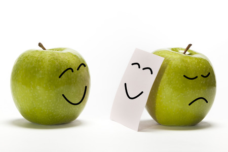 Foto de An apple smiling to other one that is concealing its sadness behind a smily mask - Imagen libre de derechos