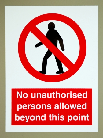 no unauthorised persons allowed beyond this  sign on a gray wall