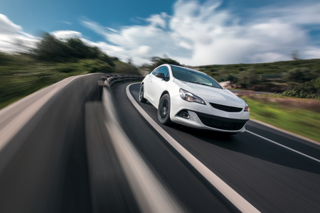 Photo pour White car cornering in mountain road with speed blur - image libre de droit