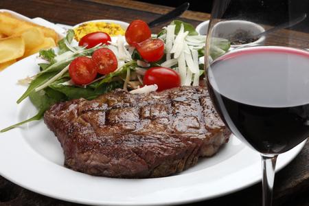 Foto de Rib fillet with salad and red wine - Imagen libre de derechos