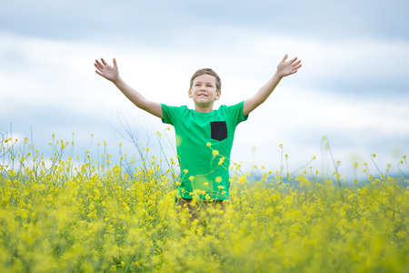 Photo for Happy cute handsome little kid boy on green grass lawn with blooming yellow dandelion flowers on sunny spring or summer day. Little boy dreaming and relaxing collecting a bouquet. - Royalty Free Image