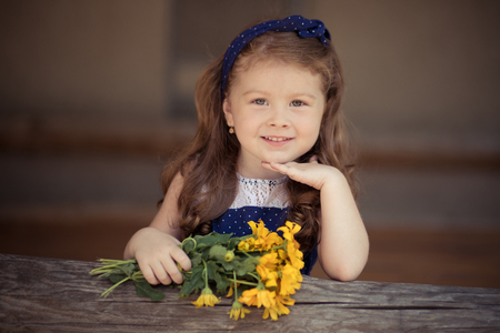 Foto de Young baby girl with brunette hairs and bright perfect skin cheeks wearing stylish awesome blue dress posing with bouquet of wild yellow flowers daisy. - Imagen libre de derechos