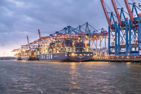 Foto per Hamburg / Germany - July 12 2017: Container gantry cranes of the terminal Burchardkai unloading ships in the deepwater port Hamburg-Waltershof at night - Immagine Royalty Free