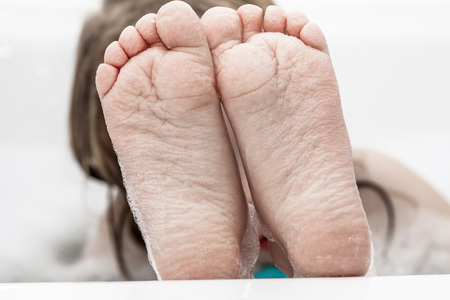 Photo pour Closeup of wrinkeled feet on edge of bubble bathtub - image libre de droit