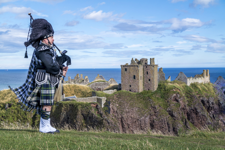 Photo for Traditional scottish bagpiper in full dress code at Dunnottar Castle in Stonehaven - Royalty Free Image