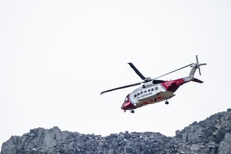Foto de Ogwen Glen / Wales - April 29 2018 : British HM Coastguard helicopter Sikorsky S-92 operated by Bristow Helicopters conducting a rescue exercise at Ogwen Glen - Imagen libre de derechos