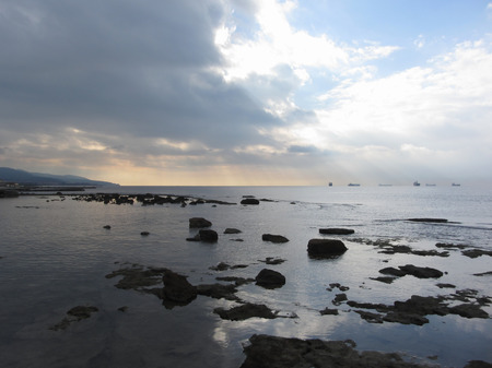 Photo for Rocks landscape sea with giants cumulonimbus clouds in the sky and cargo ships at the horizon . Livorno, Tuscany, Italy - Royalty Free Image