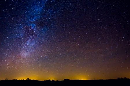 Photo for Night landscape image with colorful milky way and yellow light in the horizon - Royalty Free Image