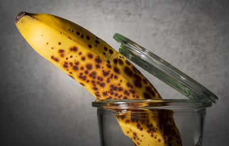 Foto de Ripe banana comes out of glass. Abstract art. - Imagen libre de derechos