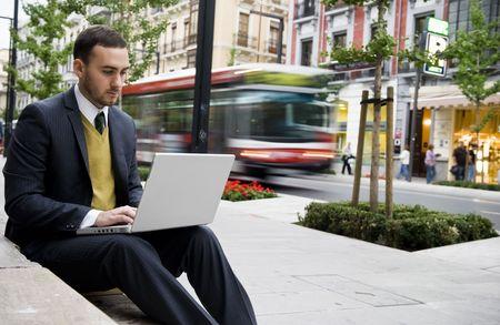 Businessman portrait with laptop in blurred urban background