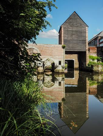 Photo pour The old wooden building Spuihuis, part of the 15th century water mill complex in   Belgium, crossing the river Dijle. - image libre de droit