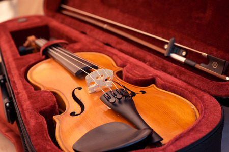 Photo for Close up of violin shallow deep of field  Violin and bow in dark red case. Close up view of violin strings and bridge - Royalty Free Image