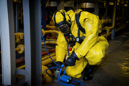 Photo pour Rescuers in a radiation protection suit. - image libre de droit