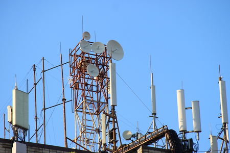 Photo pour Telecommunication base stations network repeaters on the roof of the building. The cellular communication aerial on a building roof. Cell phone telecommunication tower. Antennas on top of building - image libre de droit