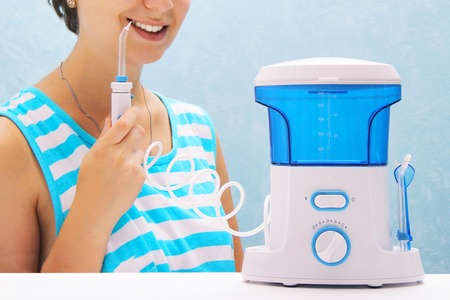 Foto per beautiful girl flushes her teeth with an oral irrigator. the woman smiles and holds the irrigator handle. cleaning of teeth at home with a compact device. Cleaning teeth with water jet under pressure. - Immagine Royalty Free