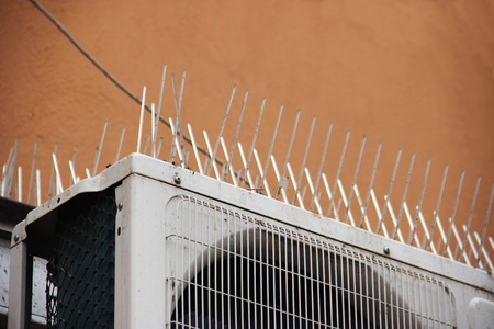 Foto de part of the facade of the building with plastic spikes against pigeons. the design does not allow birds to sit down and shit. Vertical plastic spikes in two rows keep air conditioners from droppings. - Imagen libre de derechos