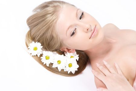 Close-up beautiful fresh young model with camomile flowers in hair
