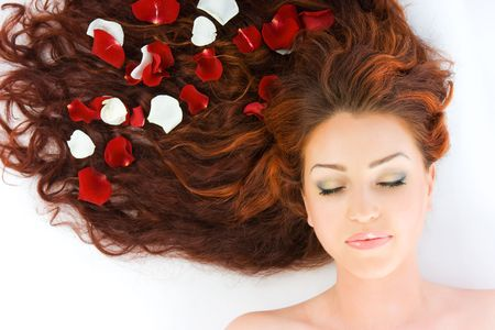 Close-up beautiful luxury fresh bright young lady lying in studio shot with rose petals in her red long hair