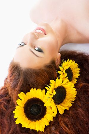 Close-up beautiful luxury fresh bright young lady in studio shot with sunflowers in her red long hair