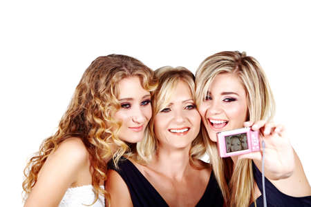 beautiful mother and daughters with make-up and long blond hair happy together on a white studio background taking picture with digital camera