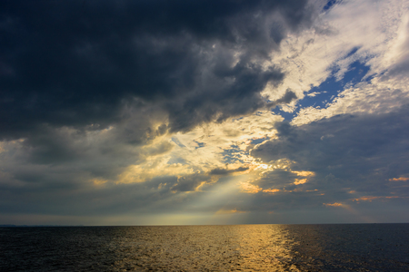 Photo for The rays of the sun, breaking through thunderclouds in the blue sky over the ocean with the yellow reflection of water - Royalty Free Image