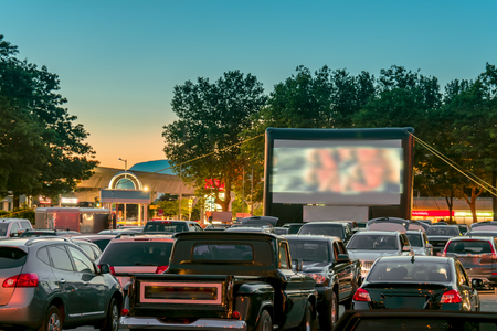 Photo for Watching movies outdoors from the car in the city parking lot on a warm summer night - Royalty Free Image