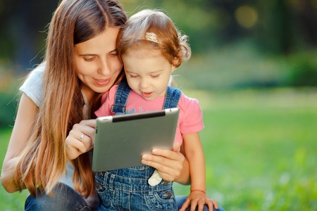 Beautiful mother and kid girl playing at tablet pc outdoors in fall. Happy mother showing her daughter funny pictures your tablet. Happy family, mother and daughter with tablet resting in the park.