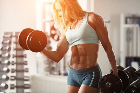 Foto de Strong woman bodybuilder with white hair and tanned body pumps up the muscles lifting dumbbells in the gym. Horizontal frame with space for text - Imagen libre de derechos