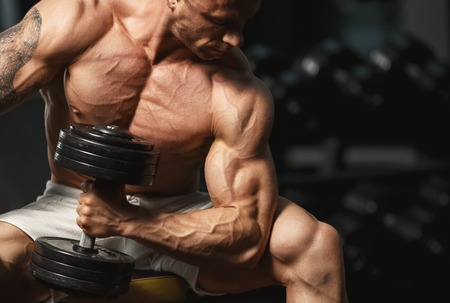 Foto de Strong muscular bodybuilder doing exercise with dumbbell in the gym - Imagen libre de derechos