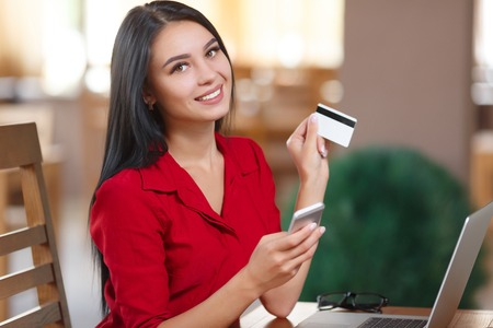 Photo pour Young business woman holding mobile phone and credit card. Woman pays for a purchase with credit card. Purchase online. Shopping online - image libre de droit