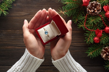 Photo for Christmas background. Engagement ring in female hands among Christmas decorations on wood background. Romance, jewelry concept - woman hands with wedding ring in gift box. Gift on Valentine's Day - Royalty Free Image