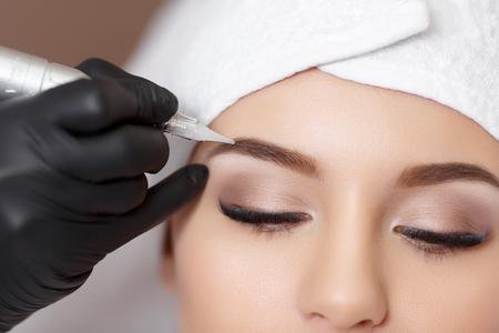 Foto de Permanent makeup. Permanent tattooing of eyebrows. Cosmetologist applying permanent make up on eyebrows- eyebrow tattoo - Imagen libre de derechos
