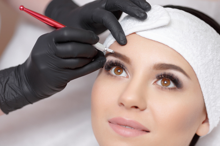 Foto de Permanent makeup eyebrows. Mikrobleyding eyebrows workflow in a beauty salon. Cosmetologist applying a special permanent makeup on a woman's eyebrows. - Imagen libre de derechos